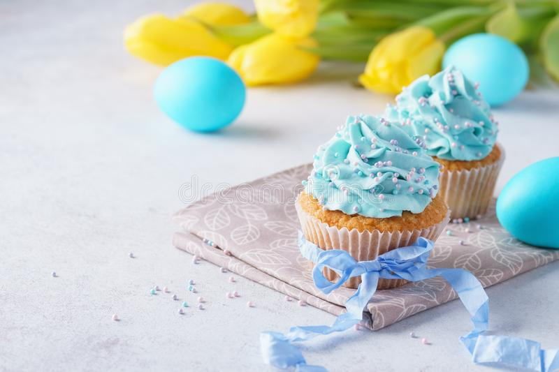 Decorated cupcakes with cream, blue eggs and tulips for Easter royalty free stock image