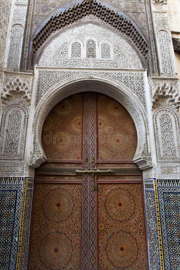 Decorated door in Fes, Morocco. Decorated door in Medersa Bou Inania, Fes Morocco royalty free stock image