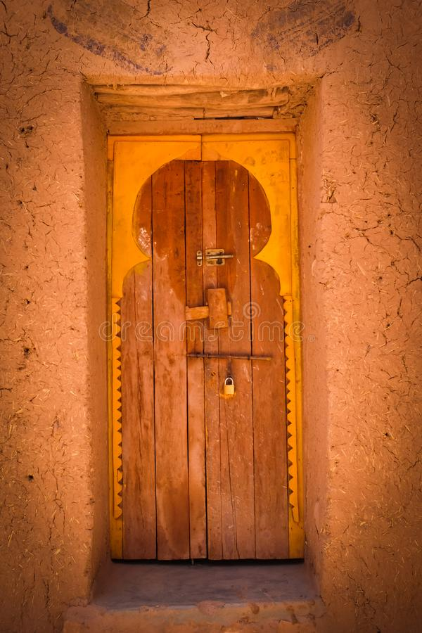 Decorative door in Morocco. A decorated door in Morocco, with padlock and orange color. Shaded from the mid-day sun, the light is diffused royalty free stock photo