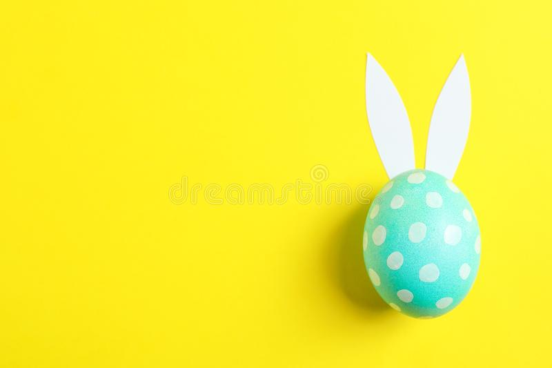 Decorated Easter egg with cute bunnies ears on yellow background stock photos