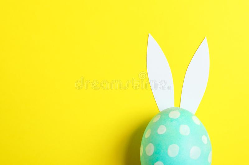 Decorated Easter egg with cute bunnies ears on yellow background stock photography
