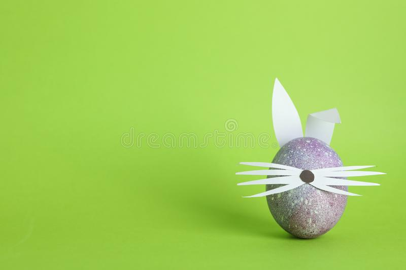 Decorated Easter egg and cute bunny`s ears on color background stock photo