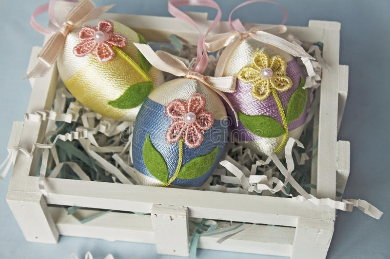 Decorated Easter eggs in a crate stock images