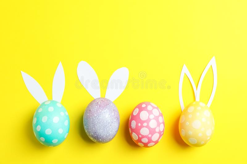 Decorated Easter eggs with cute bunnies ears on yellow background stock photos