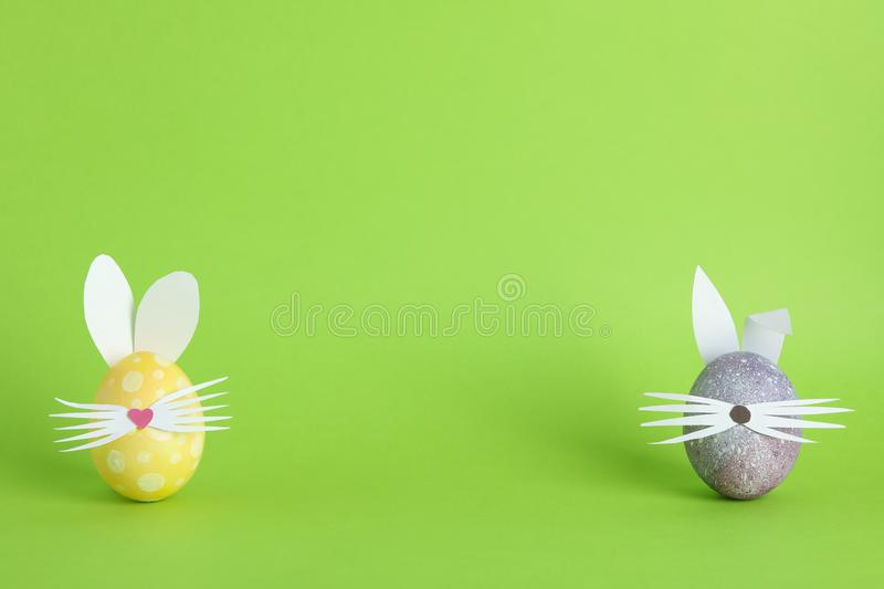 Decorated Easter eggs and cute bunny`s ears on color background royalty free stock photo