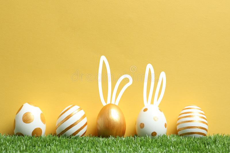 Decorated Easter eggs and cute bunny`s ears on green grass royalty free stock photos