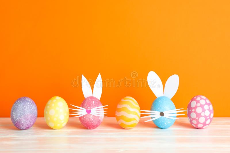 Decorated Easter eggs and cute bunny`s ears on table against color background stock image
