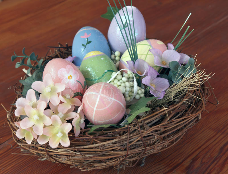 Decorated eggs. In a nest with spring flowers and greenery on wood. Easter royalty free stock images
