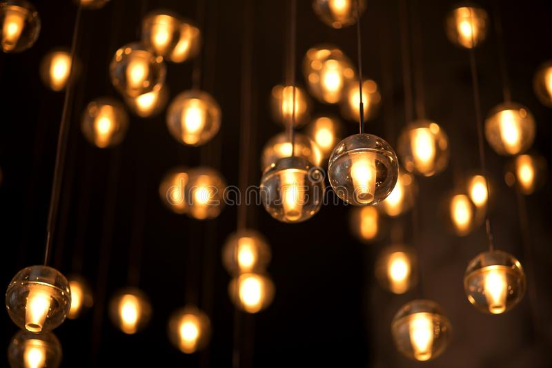 Decorated electric garland for lighting with bulbs warm white and yellow light on a dark background. Blurred background. Bulbs in royalty free stock photography
