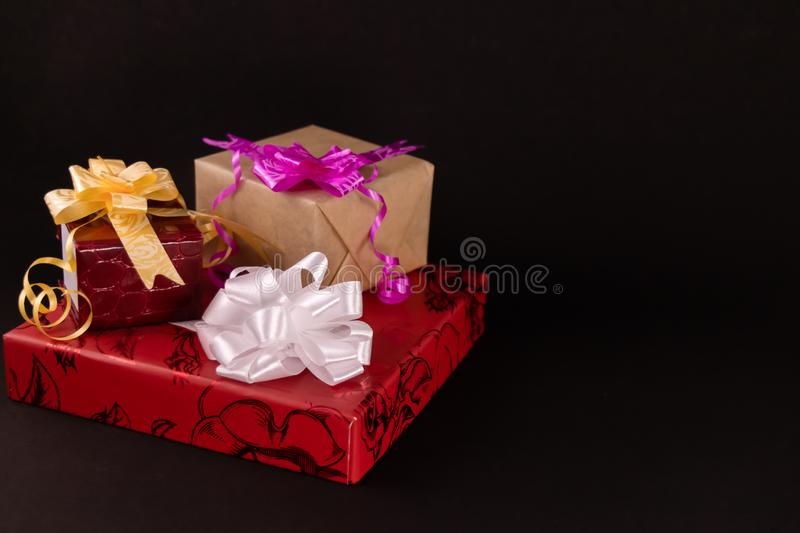 Decorated gift boxes with colorful ribbons and bows on dark contrast background. Gifts concept royalty free stock photos