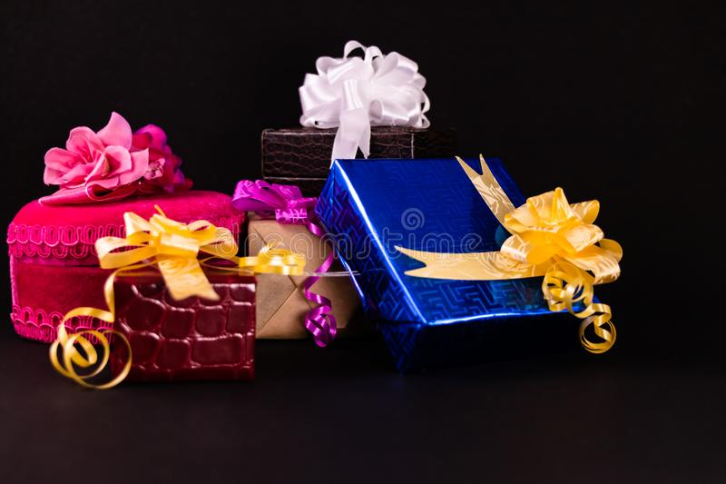 Decorated gift boxes with colorful ribbons and bows on dark surface. Gifts concept stock photography