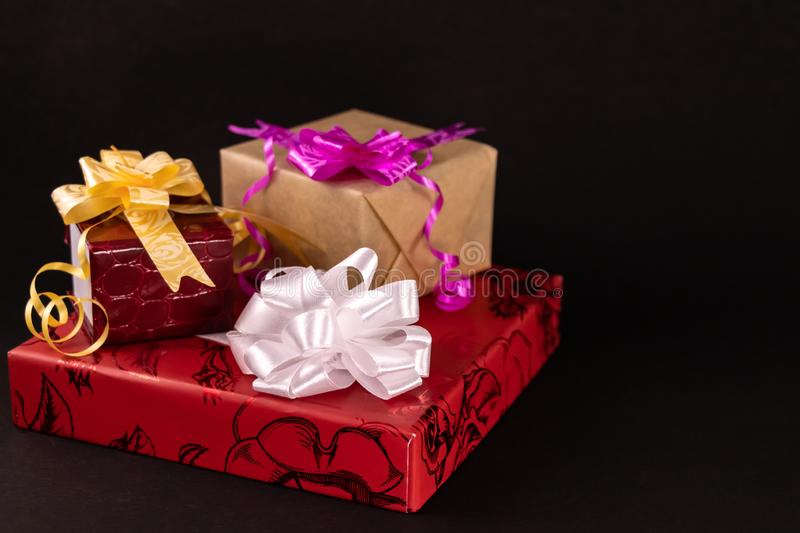 Decorated gift boxes with ribbons and bows on dark surface. Gifts for all occasions concept royalty free stock images