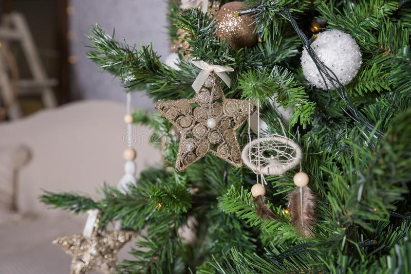 Decorated gold Christmas tree with golder patchwork ornament ,star hearts for new year in living room.Christmas and New royalty free stock photography