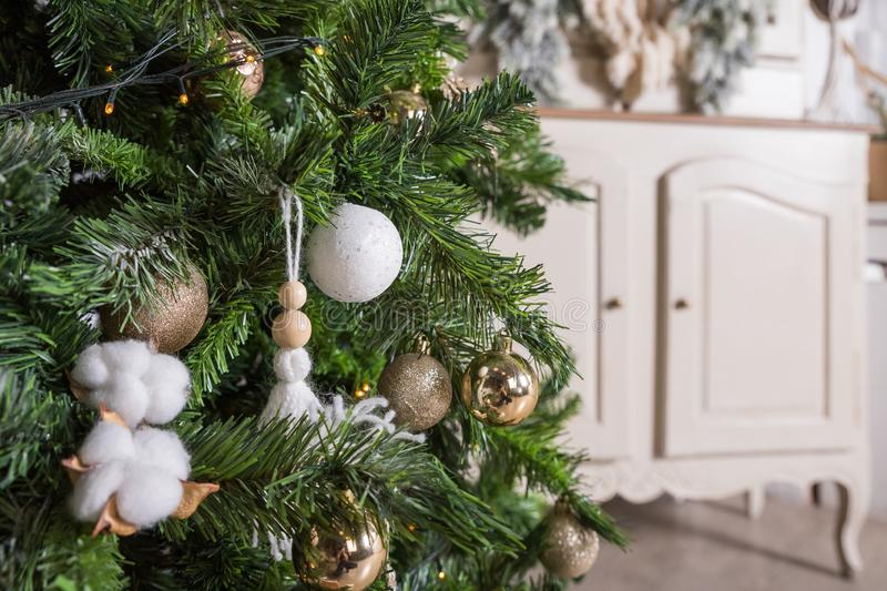 Decorated gold Christmas tree with golder patchwork ornament ,star hearts for new year in living room.Christmas and New stock images