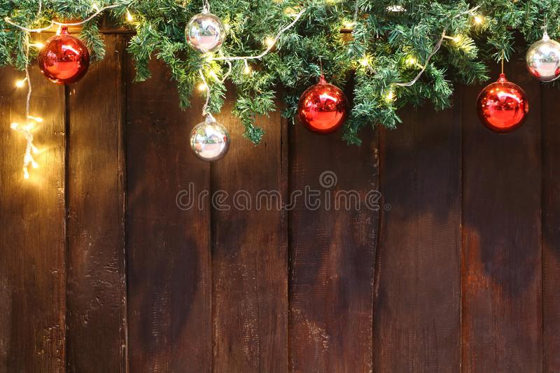 Decorated green Christmas tree branch by colorful red and silver bauble ball and yellow light on top of aged brown wood wall stock photography