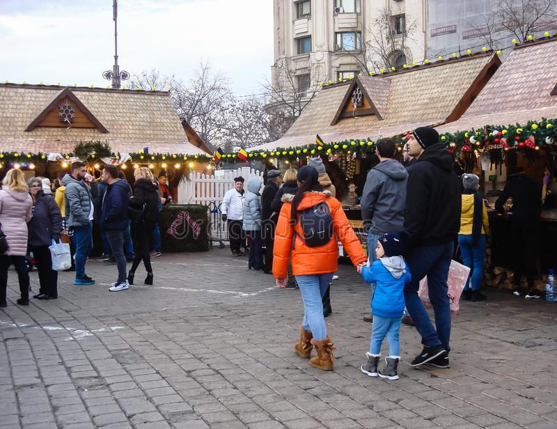 Decorated huge Christmas tree, lights, decorations, hot wine, hot chocolate, presents and people wandering at the Christmas market stock image