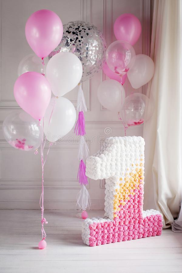 Decorated number 1 for a first birthday and balloons stock photography