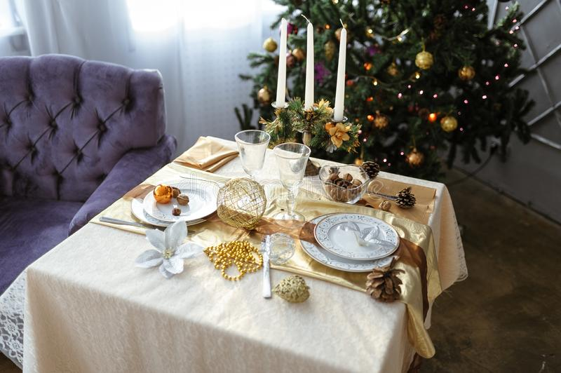 Decorated table with candles and white tablecloth on the background of a decorated Christmas tree royalty free stock photo