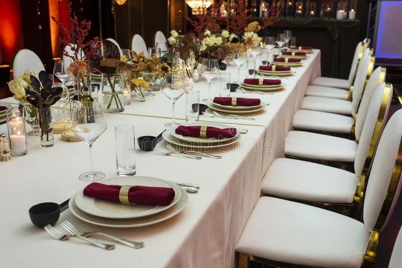 A decorated table decorated with flowers and cloth napkins. On plates in the interior of the restaurant royalty free stock image