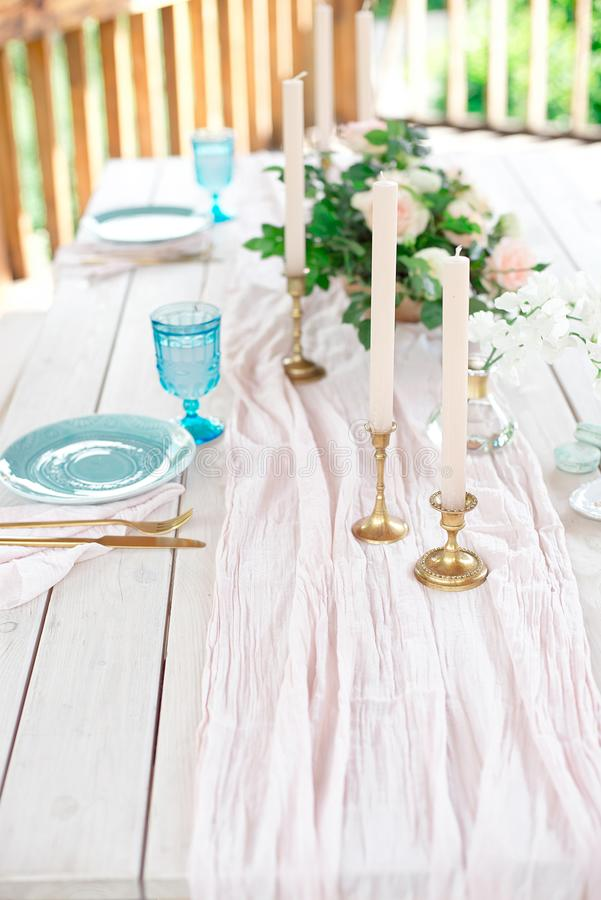 Decorated table for dinner for two person, with plates knife, fork, cheese, wine, wine glasses and flowers in a copper vase royalty free stock image