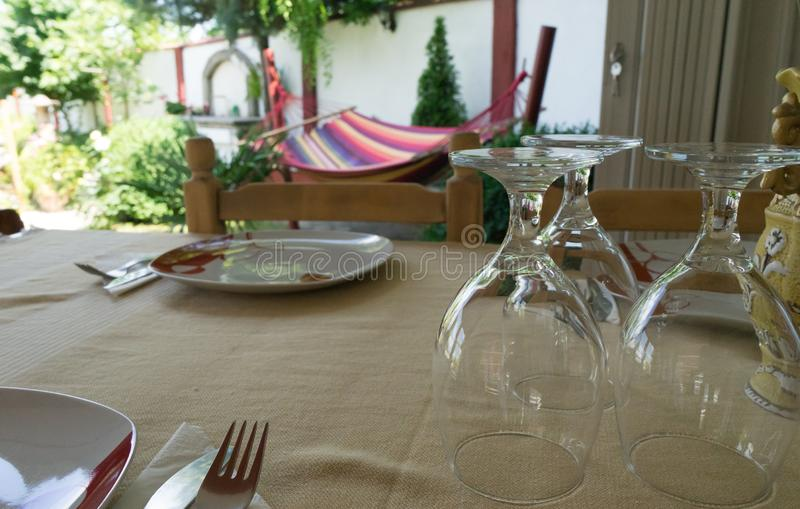 Decorated table in the garden. Dishware Decor Dinner Concept. Dishes ready and clean water cups. Hammock in summer time royalty free stock photography