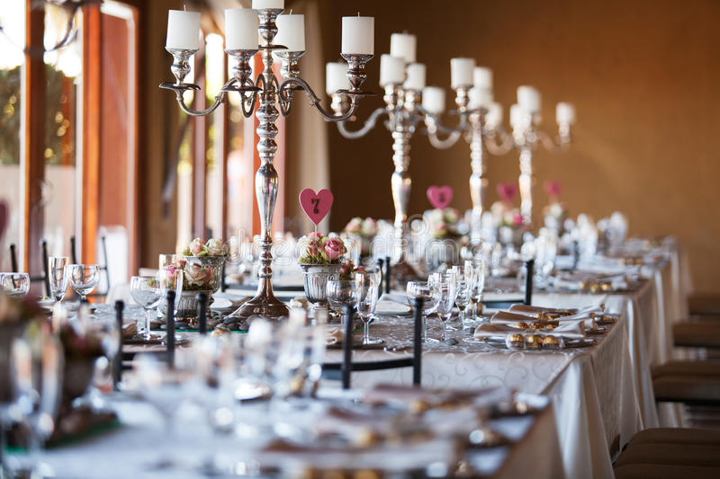 Decorated tables with candelabra at wedding reception, selective royalty free stock image