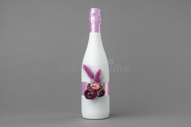 Decorated wedding bottle of champagne on gray backdrop. Decorated wedding bottle of champagne on gray background royalty free stock image