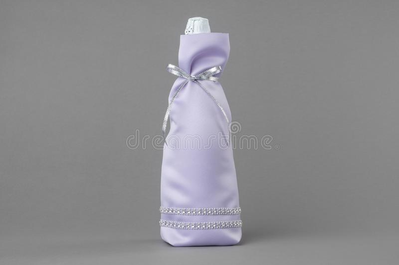 Decorated wedding champagne bottle in bag. Decorated wedding champagne bottle  in bag on gray background royalty free stock images