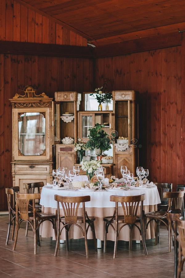 Decorated wedding table in rustic style for dinner with white and beige tablecloths, wine glasses with flowers and royalty free stock photography