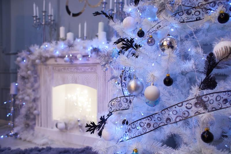 Decorated white Christmas tree in front of the fireplace stock images