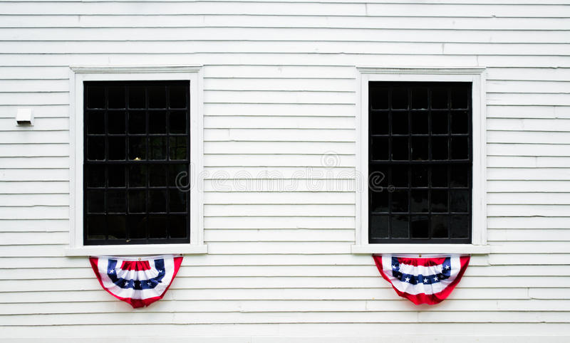 Decorated windows on a white colonial building in New England. Patriotic decorations on windows in a white colonial building in Massachusetts royalty free stock photo