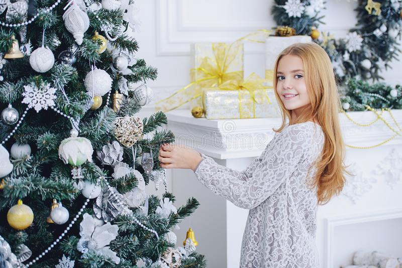 Decorates christmas tree. Happy child girl in a beautiful white dress decorates the Christmas tree. Merry Christmas and Happy New Year stock images