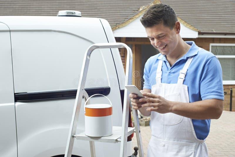 Decorateur die Mobiele Telefoon met behulp van die zich buiten Binnenlands Huis bevinden royalty-vrije stock afbeelding