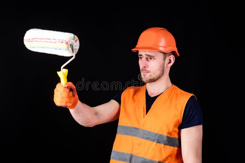 Decorateur het schilderen oppervlakte voor zich De mens in helm, bouwvakker houdt verfrol, zwarte achtergrond Verf en stock afbeeldingen