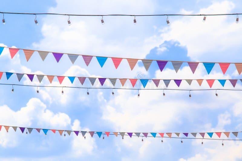 Decoratie van driehoeks de kleurrijke vlaggen bij partij of tempelmarkt met blauwe hemelachtergrond stock fotografie