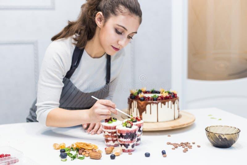 Decoratie van het gebe?indigde dessert De gebakjechef-kok bestrooit banketbakkerij met geel poeder r stock afbeeldingen