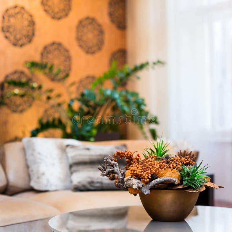 Decoratief boeket van bloemen op de lijst in oranje woonkamer stock foto