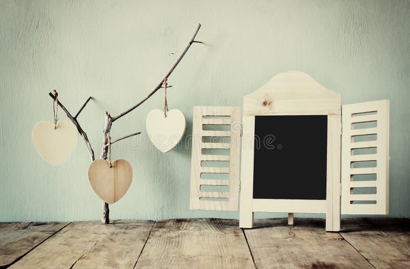 Decoratief bordkader en houten hangende harten over houten lijst royalty-vrije stock foto's