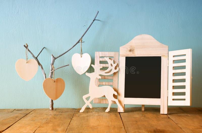 Decoratief bordkader en houten hangende harten over houten lijst klaar voor tekst of model retro gefiltreerd beeld stock foto's