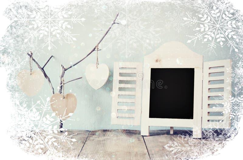 Decoratief bordkader en houten hangende harten over houten lijst klaar voor tekst of model retro gefiltreerd beeld met snowf royalty-vrije stock afbeeldingen