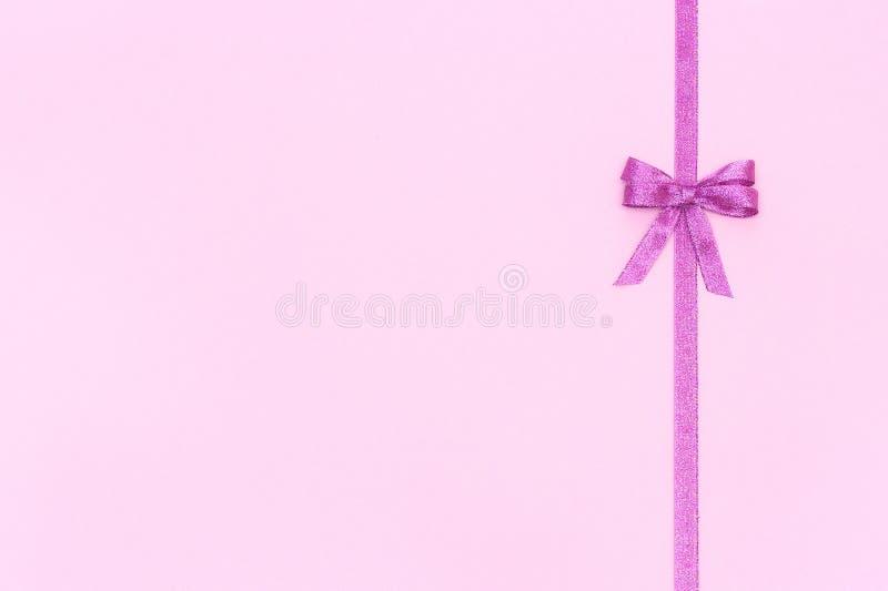 Decoratief glanzend lint met boog op pastelkleur roze achtergrond met exemplaarruimte voor tekst, Hoogste mening, Lay-out royalty-vrije stock fotografie
