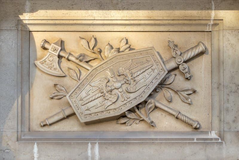 Decoratief oorlogszwaard, schild en bijl artistiek element op de gevel van een oud gebouw in Wenen, Oostenrijk stock foto's