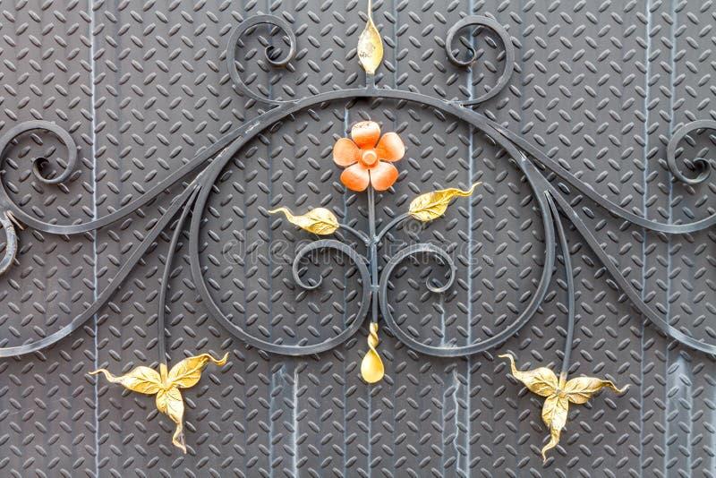 Decoratief ornament van metaaltakken, bladeren en oranje flowe royalty-vrije stock afbeelding