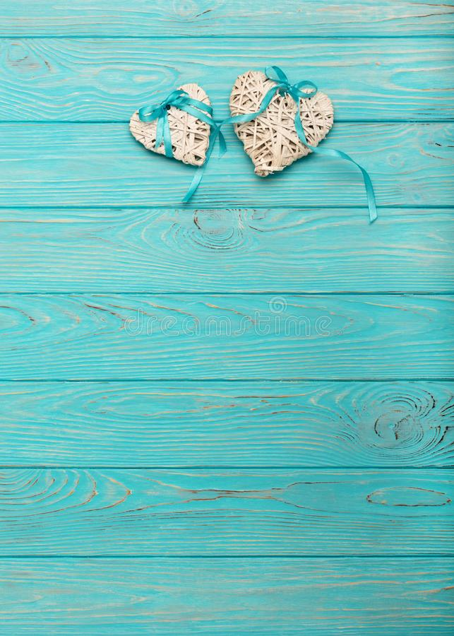 Decoratief rieten hart van grijze kleur met een blauw lint op een houten achtergrond stock foto