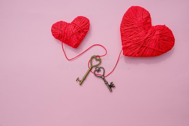 Decoratief rood hart en kleine metaalsleutel tegen roze achtergrond Feestelijk romantisch beeld voor de Dag van Valentine ` s De  royalty-vrije stock foto's