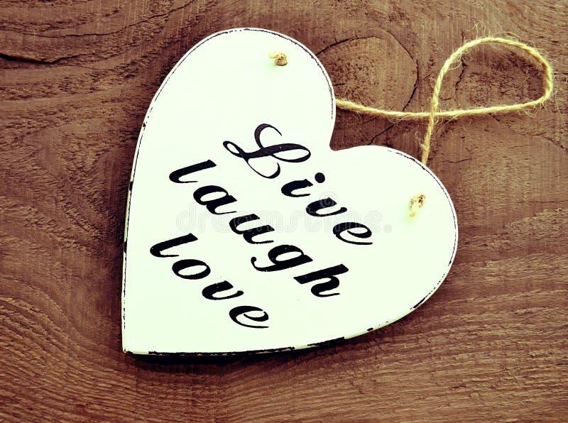 Decoratief wit houten hart met de liefde van de slogan levende lach op oude houten achtergrond Leef, Lach, Liefde stock afbeeldingen