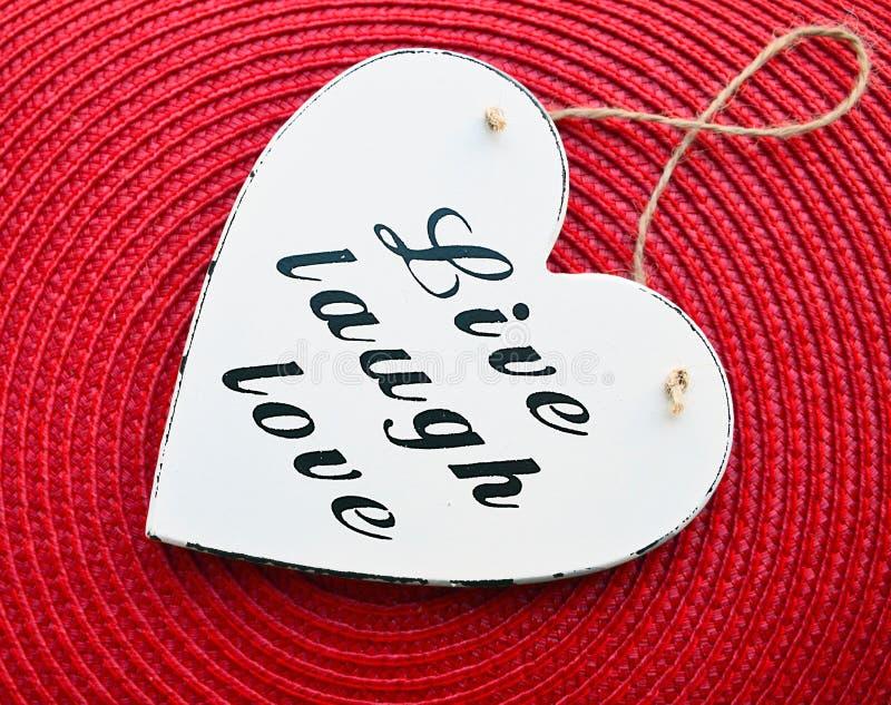 Decoratief wit houten hart met de liefde van de slogan levende lach op de rode achtergrond van het stroservet Leef, Lach, Liefde stock fotografie