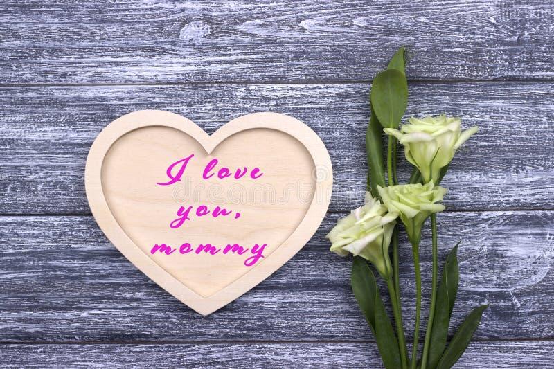 Decoratief wit houten hart op grijze houten achtergrond met het van letters voorzien Gelukkige Moeder` s Dag stock afbeelding