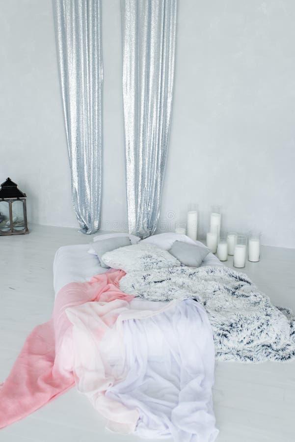 Decoratieve bedluifel in kalme en het ontspannen slaapkamer met heel wat kaarsen stock fotografie