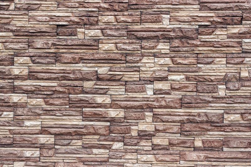 Decoratieve bruine muur van kunstmatige gescheurde steen als achtergrond o royalty-vrije stock afbeelding